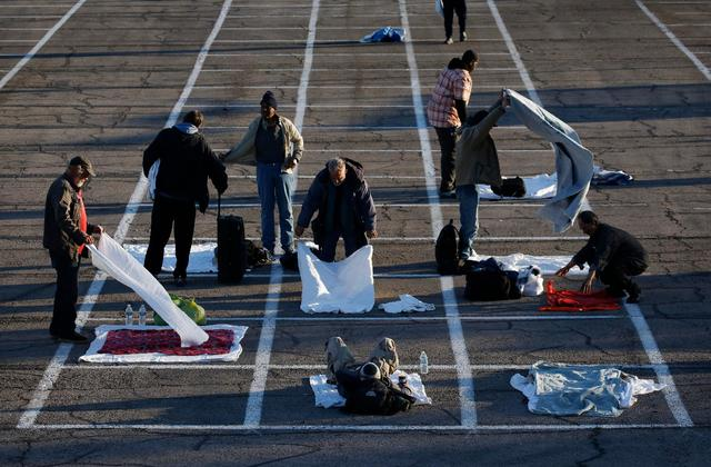 People prepare places to sleep in an area marked by painted boxes on the ground of a parking lot at a makeshift camp for the homeless, March 30, 2020, in Las Vegas. A  local shelter closed when a man staying there tested positive for the coronavirus. (Courtesy of AP Photo/John Locher)